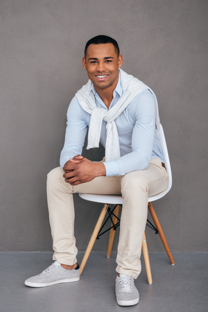 gray clothing: Confident and successful. Confident young African man sitting on the chair and smiling with grey background Stock Photo