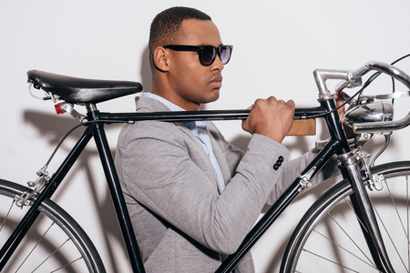 retro styled: Enjoying his style. Side view of confident young African man in sunglasses carrying his retro styled bicycle on shoulder and looking away while standing against white background