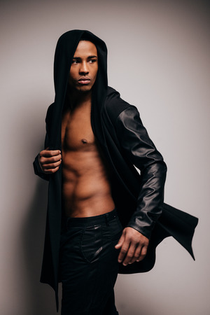 fully unbuttoned: Style in motion. Confident young African man in hooded shirt looking over shoulder while standing against grey background Stock Photo