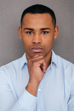 business casual: Portrait of confidence. Confident young African man holding hand on chin and looking at camera while standing against grey background
