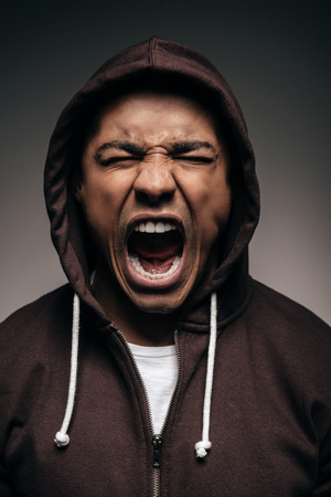 Energy inside him. Furious young African man in hooded shirt keeping eyes closed and shouting while standing against grey background