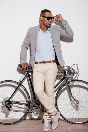 casual fashion: Confident in his perfect style. Full length of confident young African man adjusting his sunglasses and leaning at his retro styled bicycle while standing against white background Stock Photo