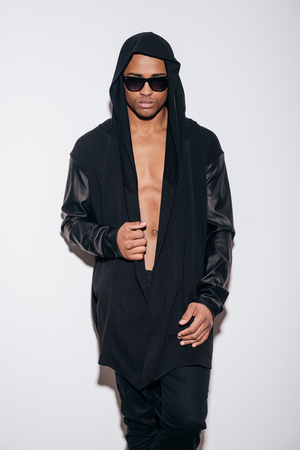 studio model: Confident in his style. Confident young African man in hooded shirt standing against white background