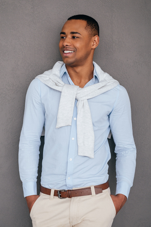 ropa casual: Young and successful. Confident young African man keeping hands in pockets and looking away while standing against grey background