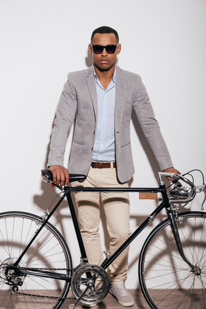 retro styled: I love my bike! Full length of confident young African man standing near his retro styled bicycle and against white background