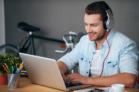 auriculares: Disfrutando de trabajo y la buena música. Alegre joven en auriculares que escucha la música mientras se está sentado en su lugar de trabajo con la bicicleta de pie en el fondo