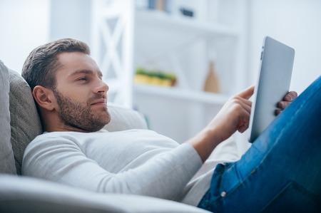 relajado: Disfrutando de su tiempo libre en casa. Vista lateral del hombre joven hermoso que trabaja en la tablilla digital y aspecto relajado mientras est� acostado en el sof� en casa