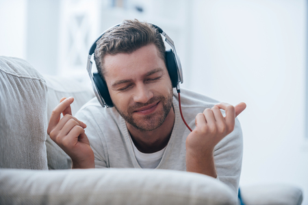 headphones: Enjoying his favorite music. Cheerful young man in headphones listening to the music and gesturing while lying on his couch at home Stock Photo