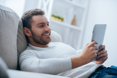 tablet: Enjoying time at home. Cheerful young man holding digital tablet and looking relaxed while lying on the couch at home