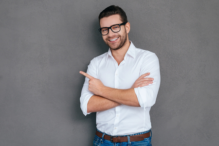 man with glasses: Look at that! Handsome young man pointing away and smiling while standing against grey background