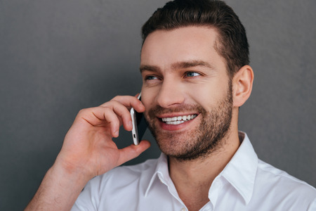 only man: Good talk. Handsome young man talking on the mobile phone and smiling while standing against grey background Stock Photo