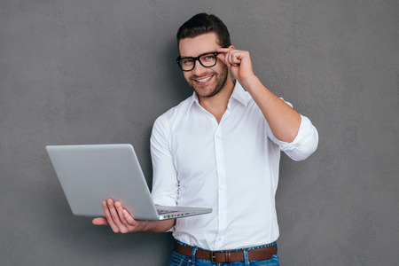 tech support: How may I help you? Handsome young man holding laptop and smiling while standing against grey background