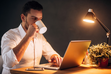 energy work: Rebooting his energy to work more. Confident young man drinking coffee while sitting at his working place at night time
