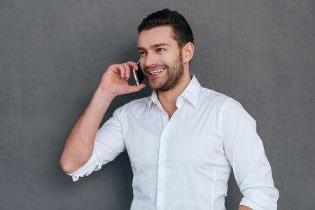 beau mec: Bonne parler affaires. Beau jeune homme parle au téléphone mobile et souriant tout en se tenant sur fond gris Banque d'images