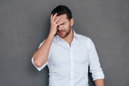 volto uomo: Oh no! Frustrato giovane uomo che copre il viso con la mano e gli occhi mantenendo chiusi, mentre in piedi contro sfondo grigio