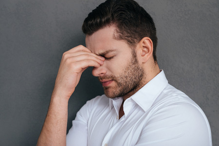 young adult men: Feeling tired and depressed. Frustrated young man touching his face with hand and keeping eyes closed while standing against grey background