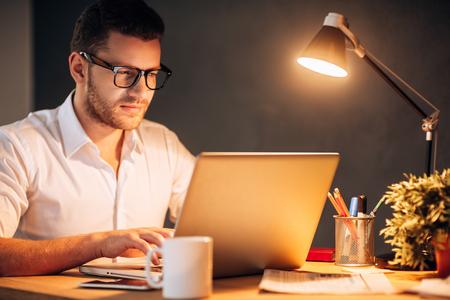 Atrapado en el cargo. Seguro de joven en gafas trabajando en su computadora portátil mientras está sentado en su lugar de trabajo durante la noche Foto de archivo - 48135682