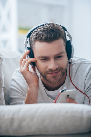 only man: I love this song. Handsome young man in headphones listening to the music and looking at his smart phone while lying on his couch at home Stock Photo