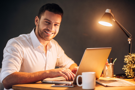 people on computers: Enjoying his work even at night. Confident young man looking at camera and smiling while sitting at his working place at night time
