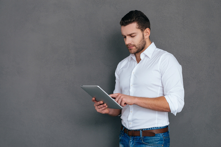 it: IT professional. Handsome young man holding digital tablet while standing against grey background
