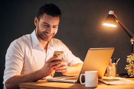 job: Buenas noticias desde colega. Hombre joven confidente que mira su teléfono inteligente y sonriendo mientras estaba sentado en su puesto de trabajo por la noche