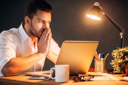hombre pensando: Pensando en solución. Hombre joven pensativo sosteniendo las manos juntas cerca de la cara mientras estaba sentado en su puesto de trabajo por la noche