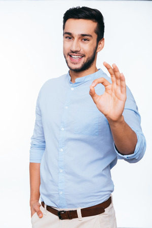 showing: Everything is OK! Confident young Indian man gesturing OK sign and smiling while standing against white background