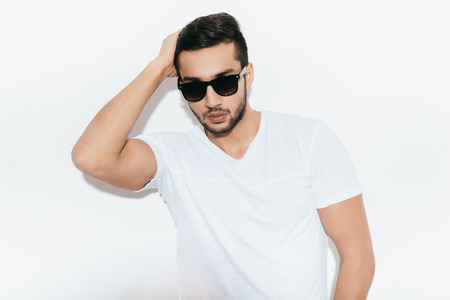 only one man: Looking good and feeling confident. Handsome young Indian man in sunglasses holding hand in hair and looking at camera while standing against white background Stock Photo