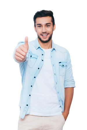 showing: Good job! Happy young Indian man showing his thumb up and smiling while standing against white background