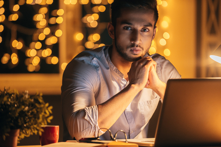 dark side: Working late again. Handsome young man holding hands clasped and looking at camera while sitting at his working place at night time with Christmas lights in the background Stock Photo