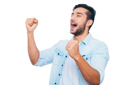 puños cerrados: Se utiliza para ganar. joven indio gesticular feliz y sonriente, manteniendo los ojos cerrados y de pie contra el fondo blanco Foto de archivo