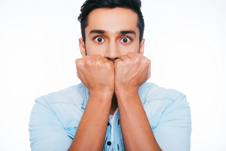 fear face: Feeling shocked and terrified. Terrified young Indian man holding fists near face and staring at you while standing against white background Stock Photo