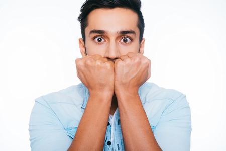 Se sentir choqué et terrifié. Terrifié jeune homme indien tenant poings près du visage et vous regardent en se tenant debout sur le fond blanc Banque d'images