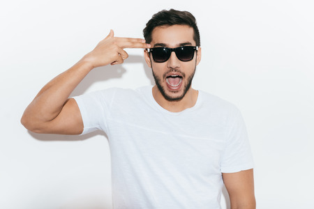 white playful: Bang! Playful young Indian man in sunglasses gesturing handgun near head and making a face while standing against white background