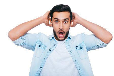 sorpresa: ¡Oh, no! Conmocionado joven india que sostiene las manos detrás de la cabeza y mantener la boca abierta mientras está de pie contra el fondo blanco Foto de archivo