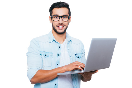 men standing: Always ready to help. Confident young Indian man holding laptop and smiling while standing against white background