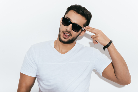 white playful: Bang! Playful young Indian man in sunglasses gesturing handgun near head and looking at camera while standing against white background
