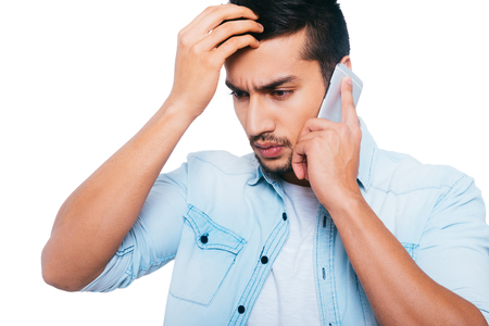 bad news: Bad news. Frustrated young Indian man talking on the mobile phone and holding hand in hair while standing against white background
