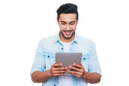 white man: Examining his brand new gadget. Handsome young Indian man holding digital tablet and looking at it with smile while standing against white background Stock Photo