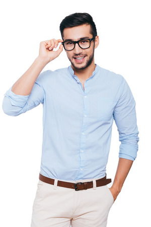 Charming handsome. Confident young Indian man adjusting his eyeglasses and smiling while standing against white background 스톡 콘텐츠