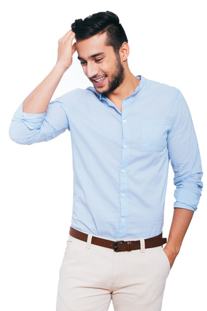 Used to look perfect. Handsome young Indian man holding hand in hair and smiling while standing against white background Archivio Fotografico
