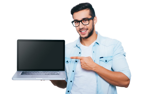 This is what you need! Confident young Indian man carrying laptop on hand and pointing it while standing against white background