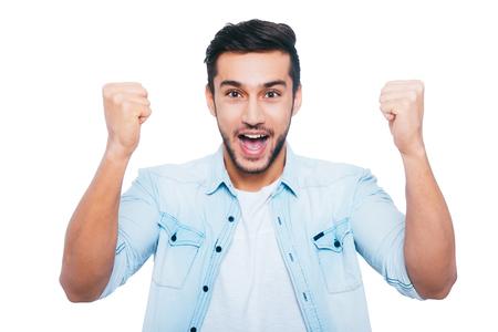 Ik heb gewonnen! Gelukkig jonge Indiase man gebaren en glimlachen terwijl staande tegen een witte achtergrond Stockfoto