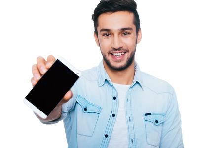 confianza: Espacio en blanco en su tel�fono inteligente. Hombre indio joven confidente que muestra su tel�fono inteligente y sonriendo mientras est� de pie contra el fondo blanco Foto de archivo