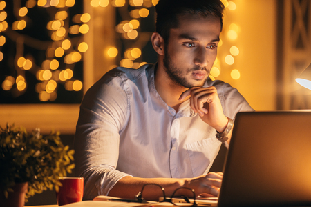 man with laptop: Working late. Confident young man working on his laptop while sitting at his working place at night time with Christmas lights in the background Stock Photo