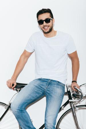 hombres jovenes: Disfrutando de su estilo. apuesto joven indio con gafas de sol que se inclina a su estilo retro bicicleta y sonriendo mientras está de pie contra el fondo blanco Foto de archivo