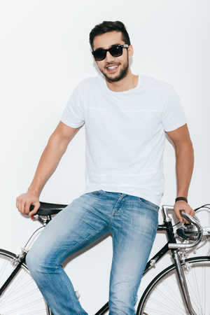 retro styled: Enjoying his style. Handsome young Indian man in sunglasses leaning at his retro styled bicycle and smiling while standing against white background