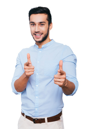 men standing: I choose you! Confident young Indian man pointing you and smiling while standing against white background