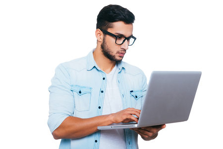 laptop stand: IT professional at work. Confident young Indian man working on laptop while standing against white background