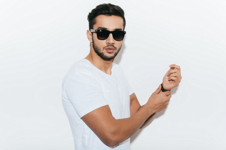 white shirt: Cool and trendy. Side view of handsome young Indian man adjusting his bracelet and looking at camera while standing against white background
